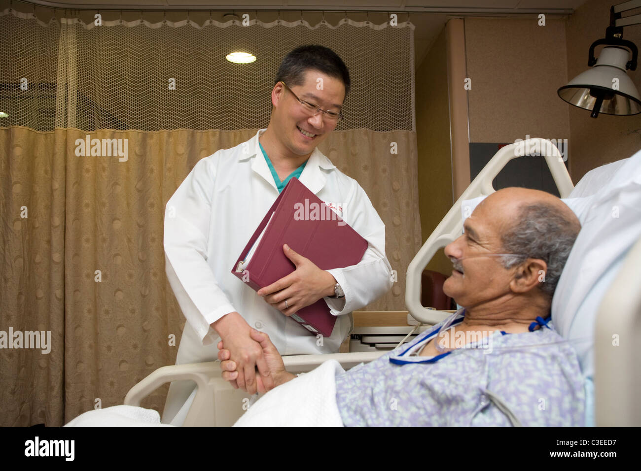 Doctor reassures older patient that he is doing well after surgery. - Stock Image