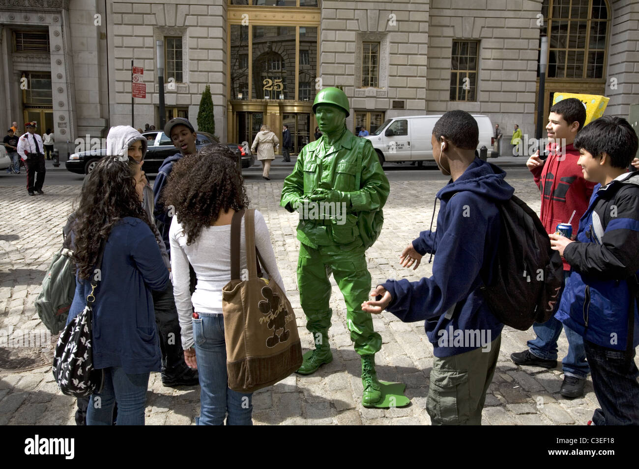 Street performer dressed as a 'GI sculpture' enthralls a group of young teenagers in Lower Manhattan. - Stock Image