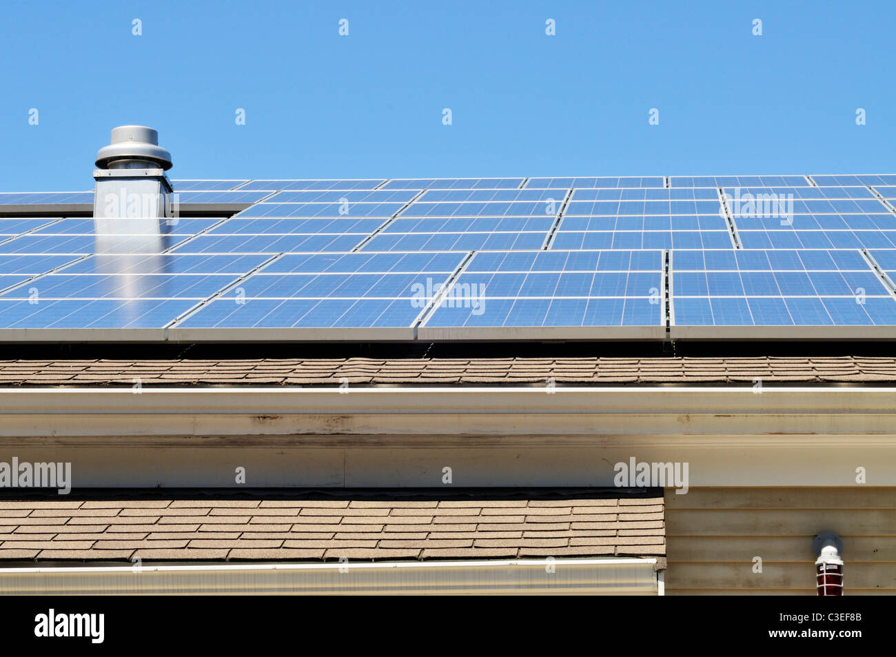 Solar panels on roof of building on a sunny blue sky day - Stock Image