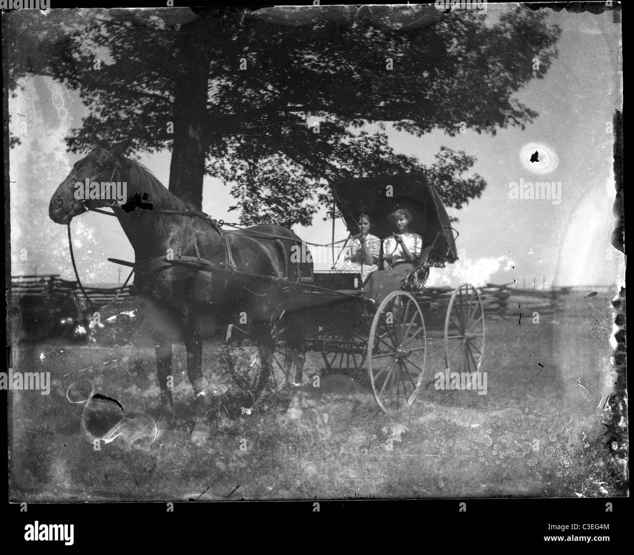 two women sitting in a horse and buggy dirt street road house transportation 19th century 1890s - Stock Image