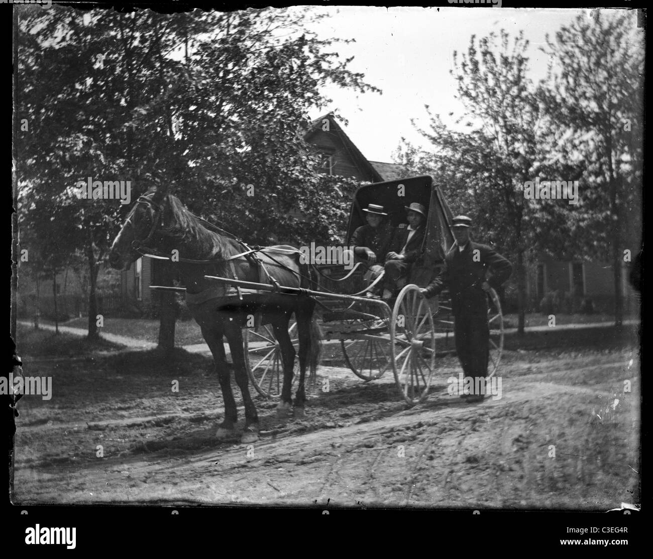 two men sitting in a horse and buggy dirt street road house transportation 19th century 1890s - Stock Image