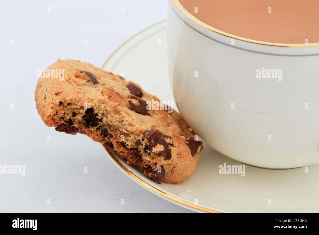 Cup of English tea and a chocolate chip biscuit with a bite taken out on the saucer. England UK Britain - Stock Image