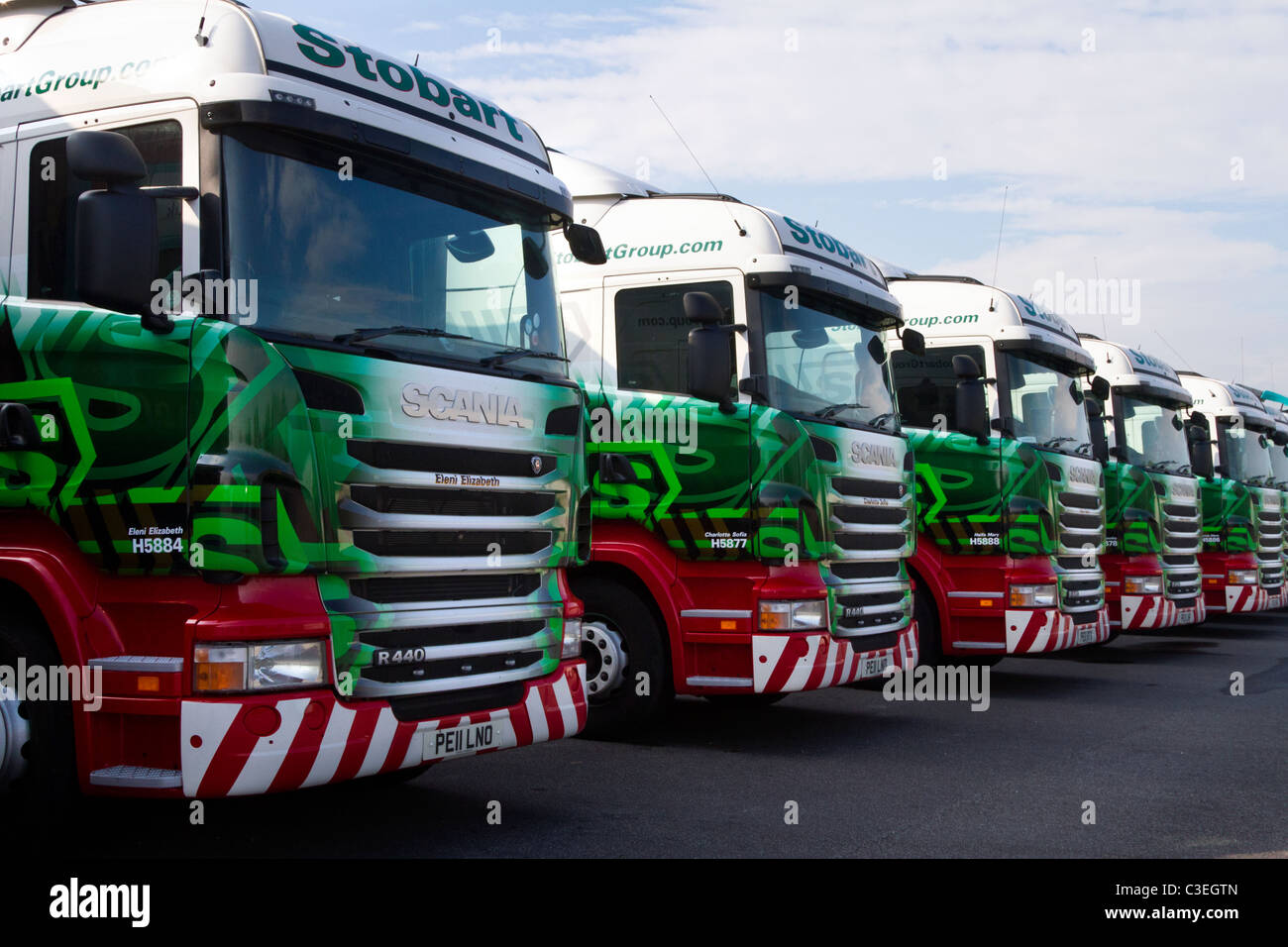 Row of Parked Eddie Stobart trucks trailers & containers at Lorry Halt  Row of Livery AEC Scania 440 haulage vehicles. Stock Photo