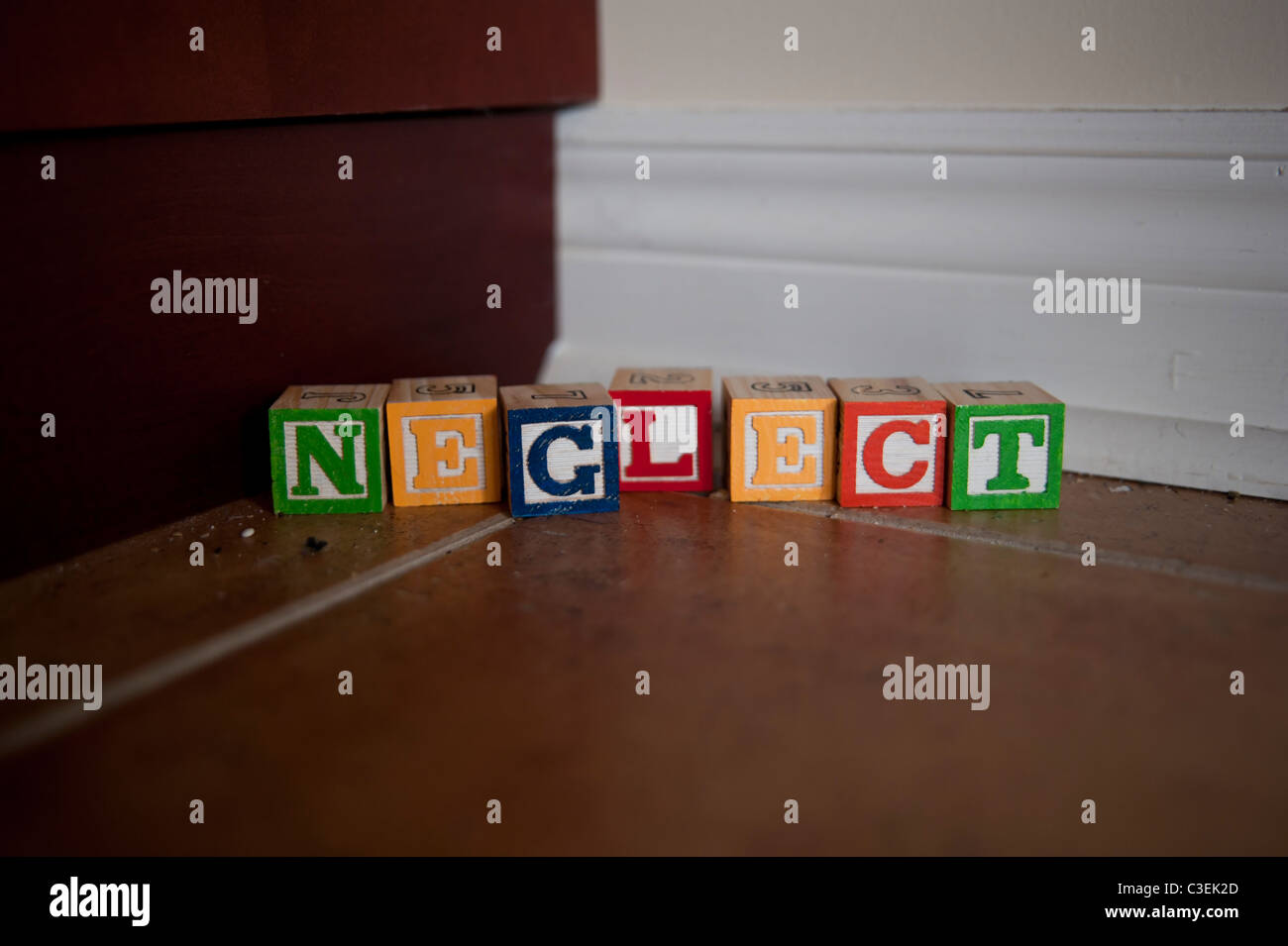 The word neglect spelled out in colourful children's blocks in a dusty corner of the house. - Stock Image