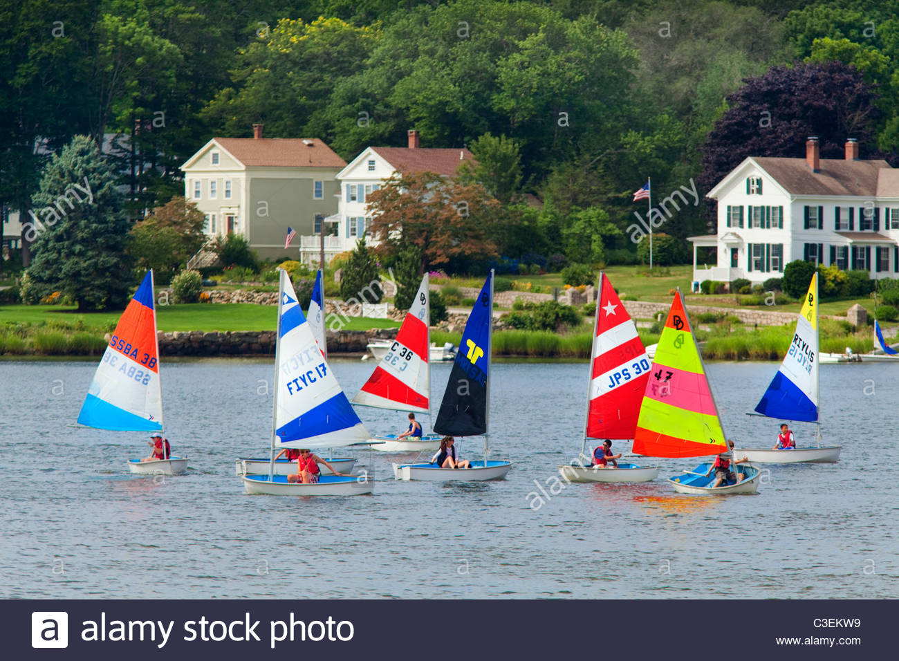 Children in fleet of racing sailboats in the Mystic River, with historic houses in background. Mystic, Connecticut - Stock Image