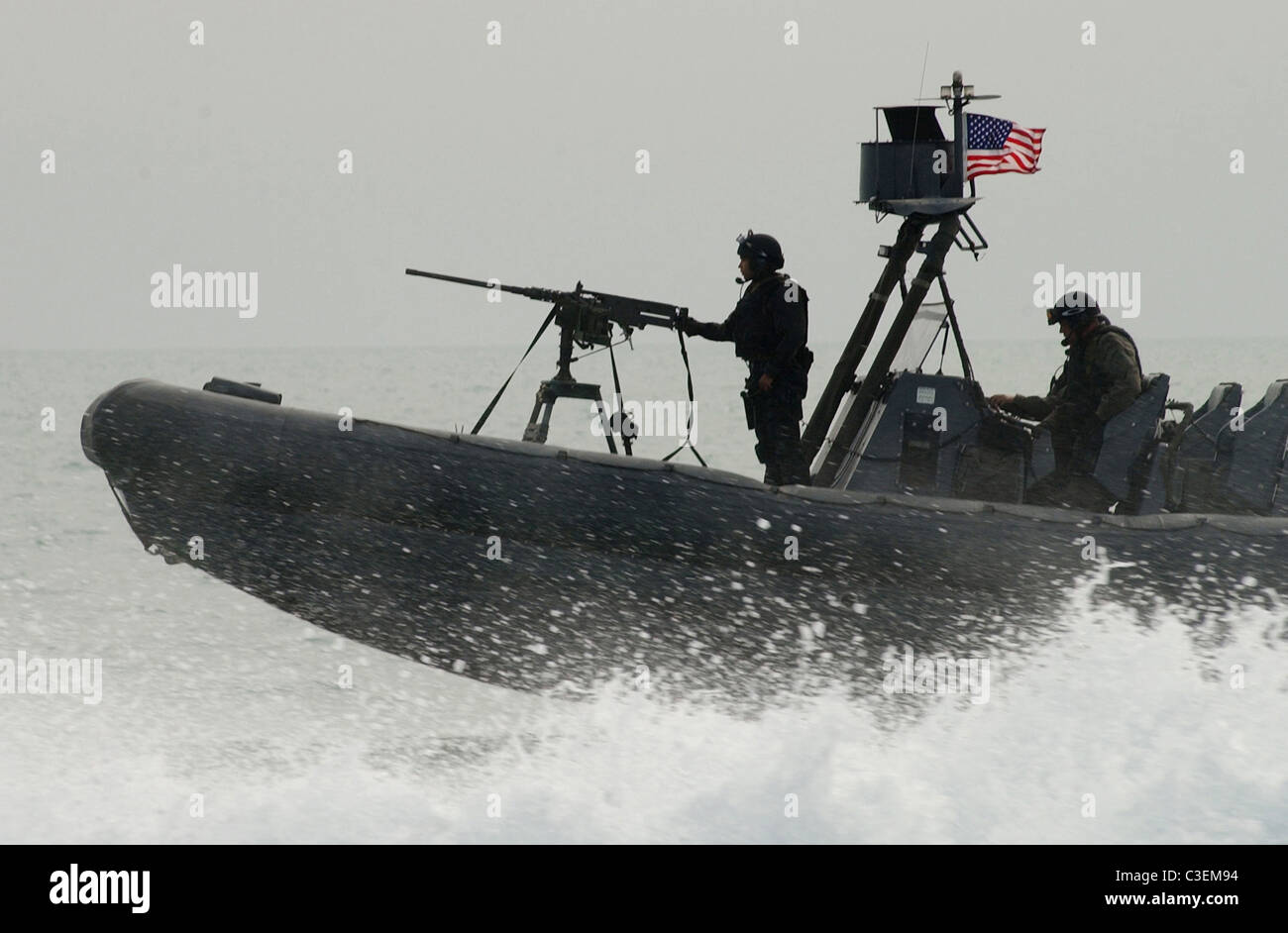 Naval Special Warfare combatant craft crewmen, SEALS operate a Rigid Hull Inflatable Boat from a forward location. - Stock Image