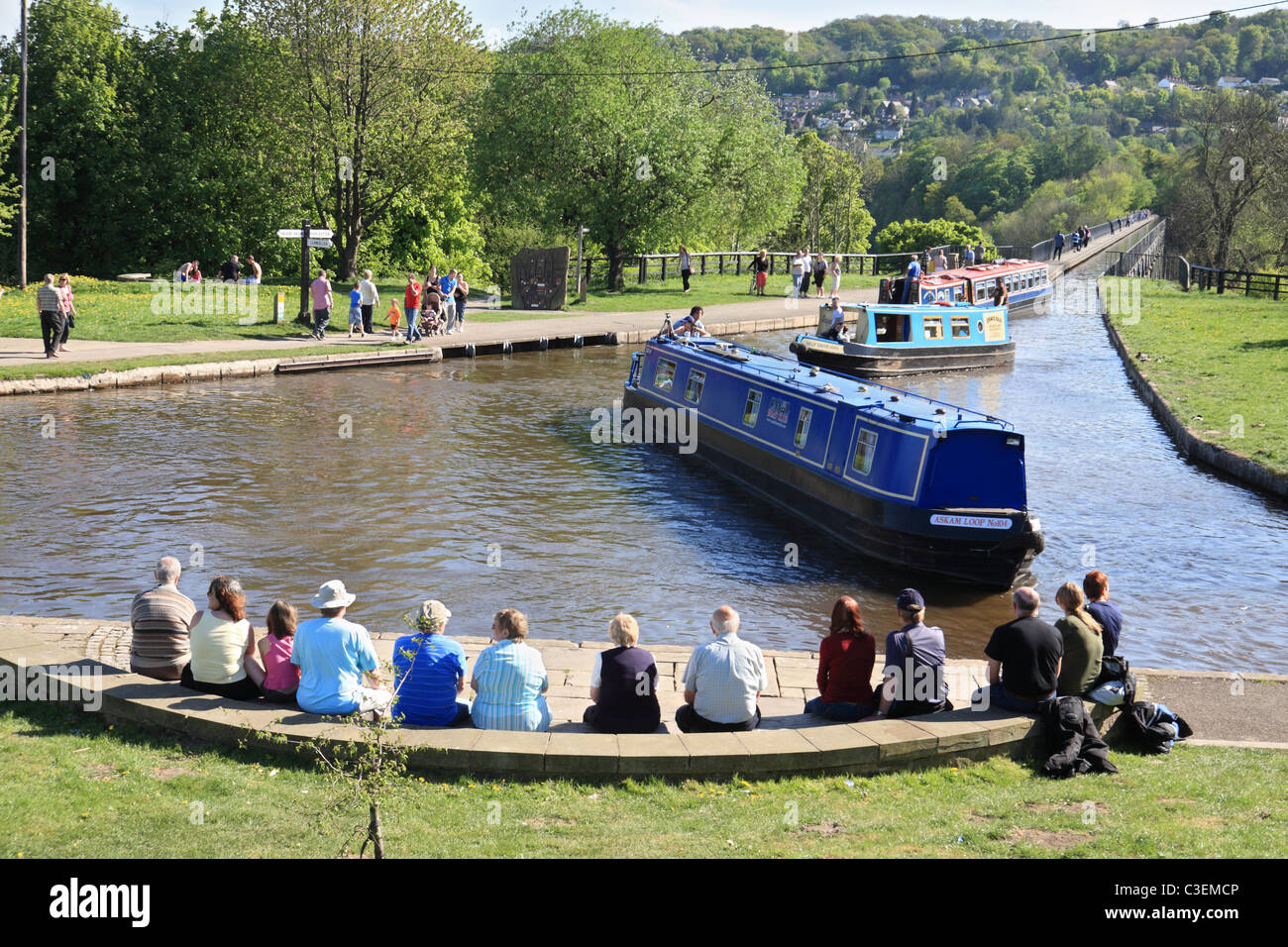 People watching canal boats crossing Pontcysyllte Aqueduct then entering Trefor Basin on the  Llangollen Canal, Stock Photo