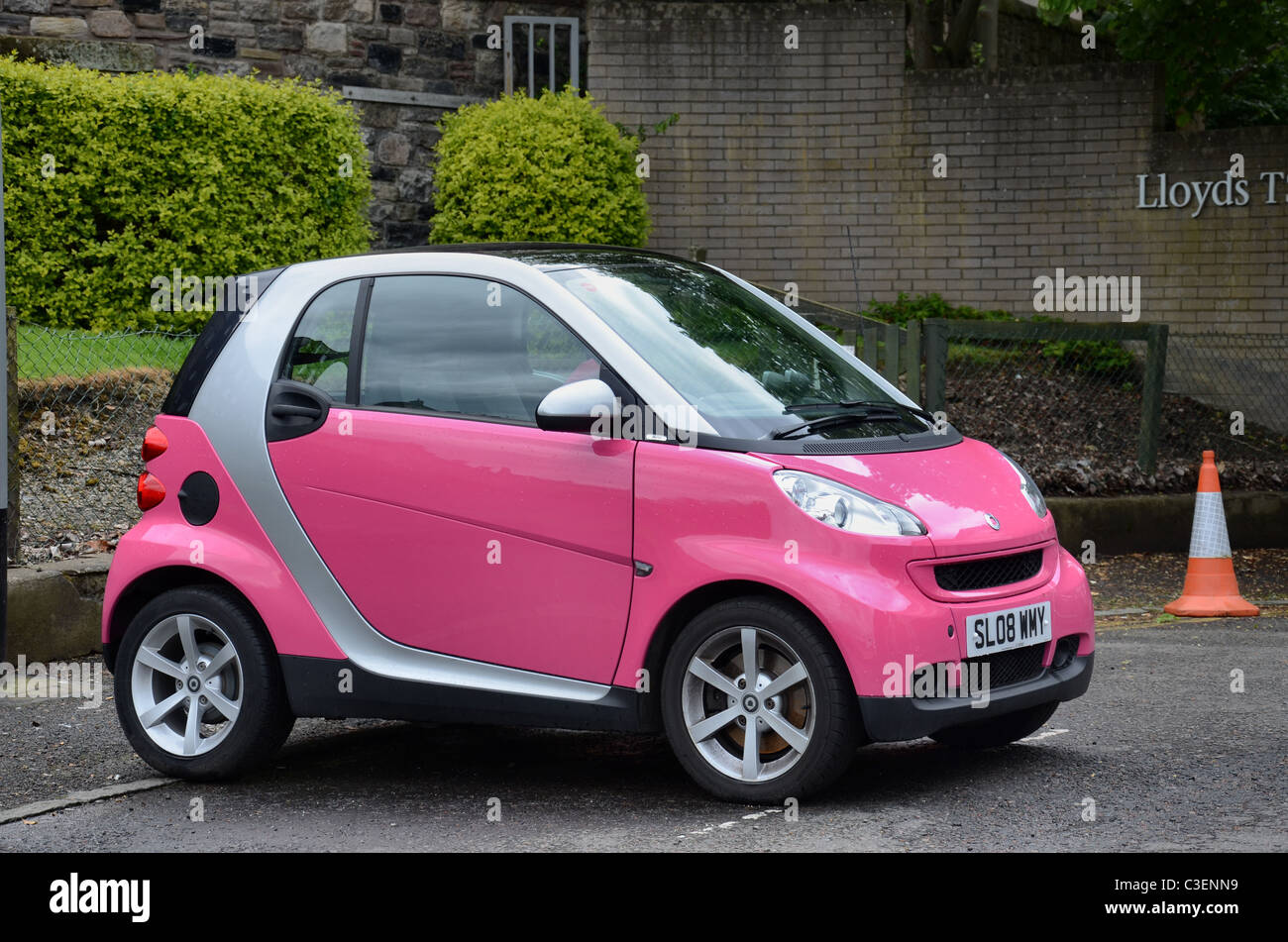 A pink and silver Smart Car parked outside Lloyds Banking Group offices in Edinburgh. - Stock Image