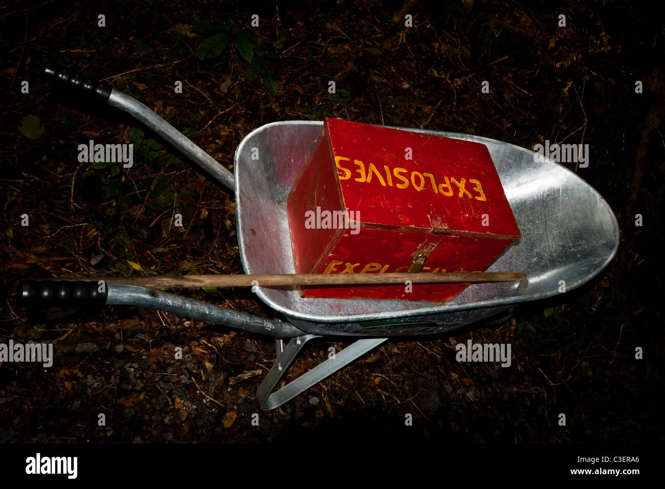 Barrow with red wooden box full of explosives in dark forest. - Stock Image