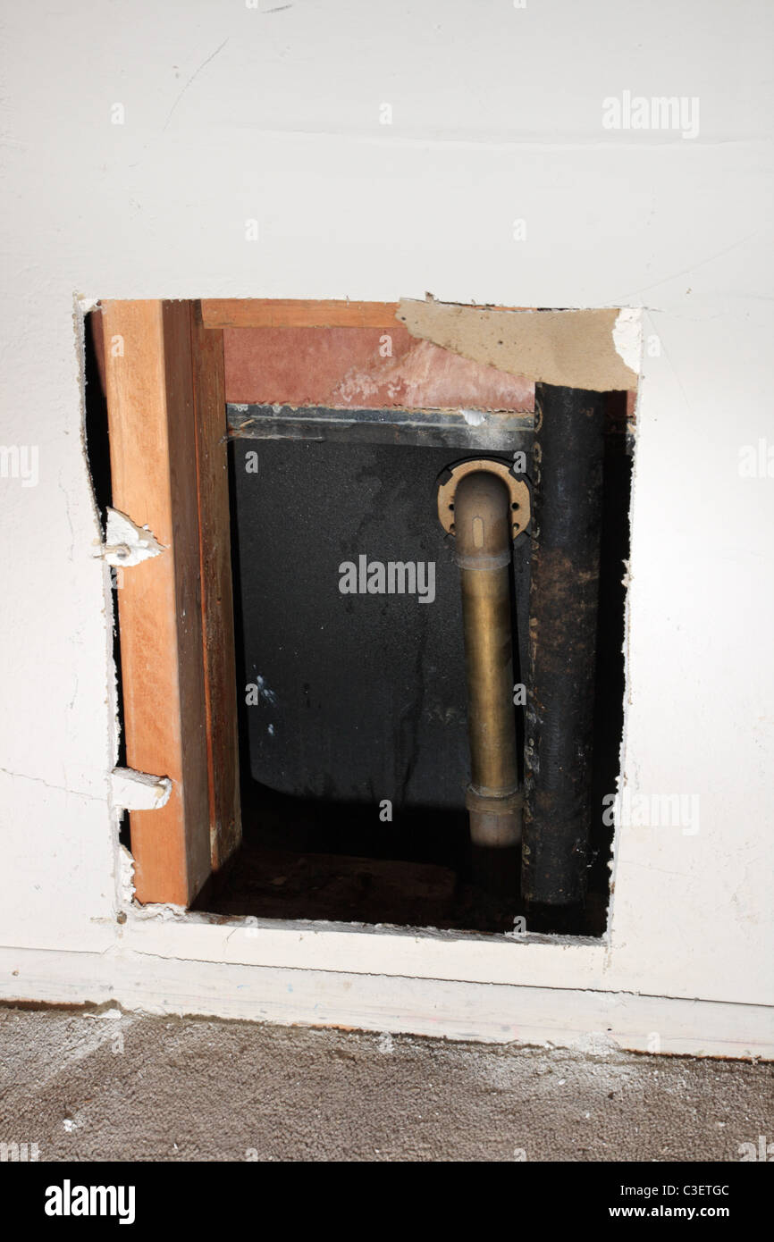 hole in drywall to expose bathtub drain plumbing - Stock Image
