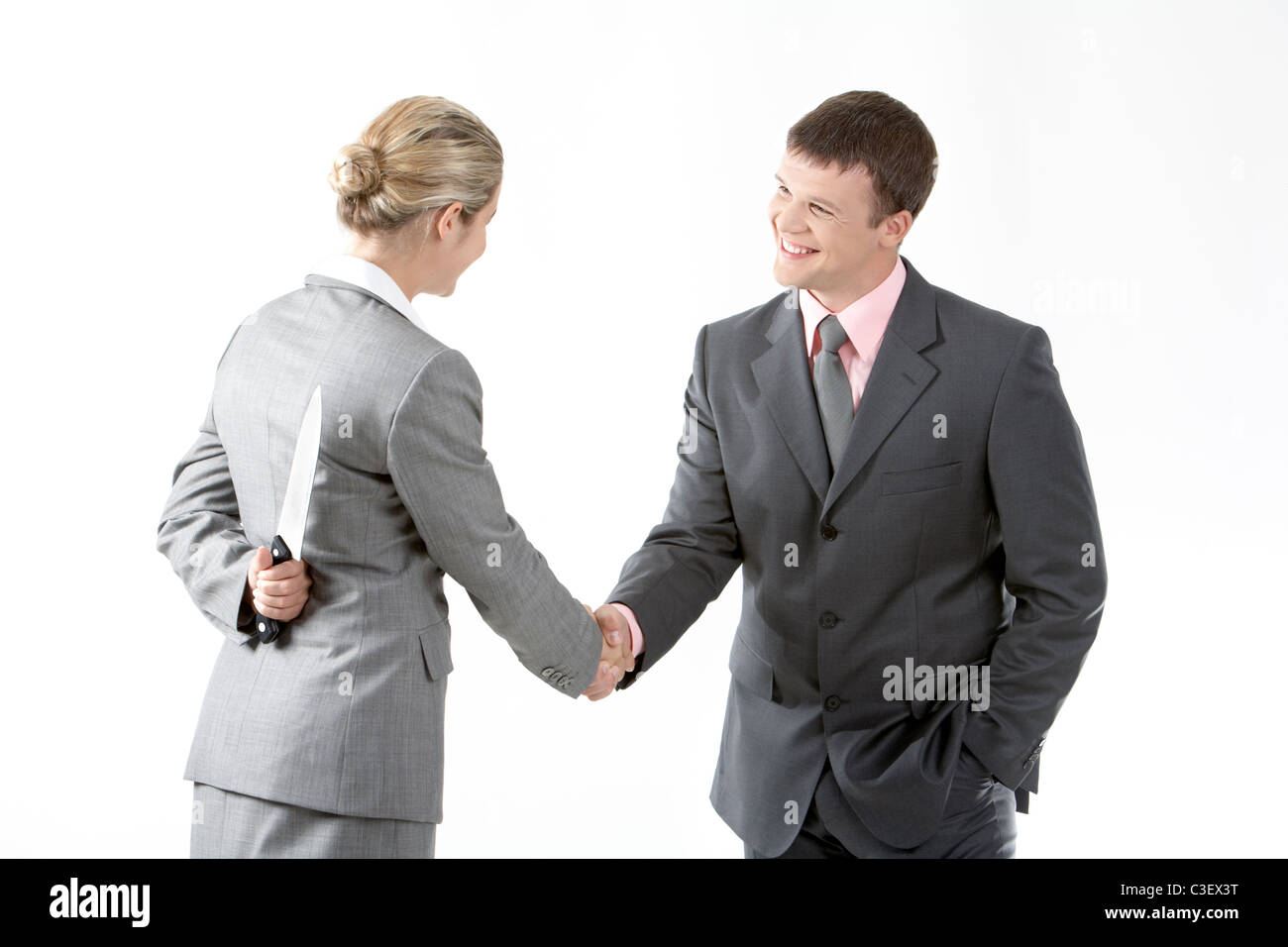 Portrait of business partners handshaking while female holding knife behind her back - Stock Image