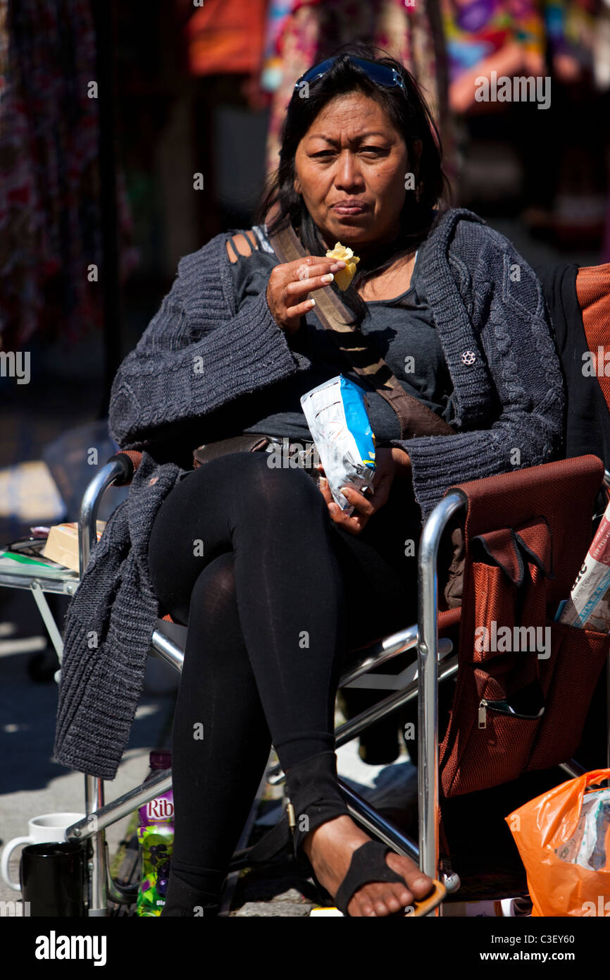 Bolivian woman eating a bag of crisps by Little Venice, London, England, UK - Stock Image