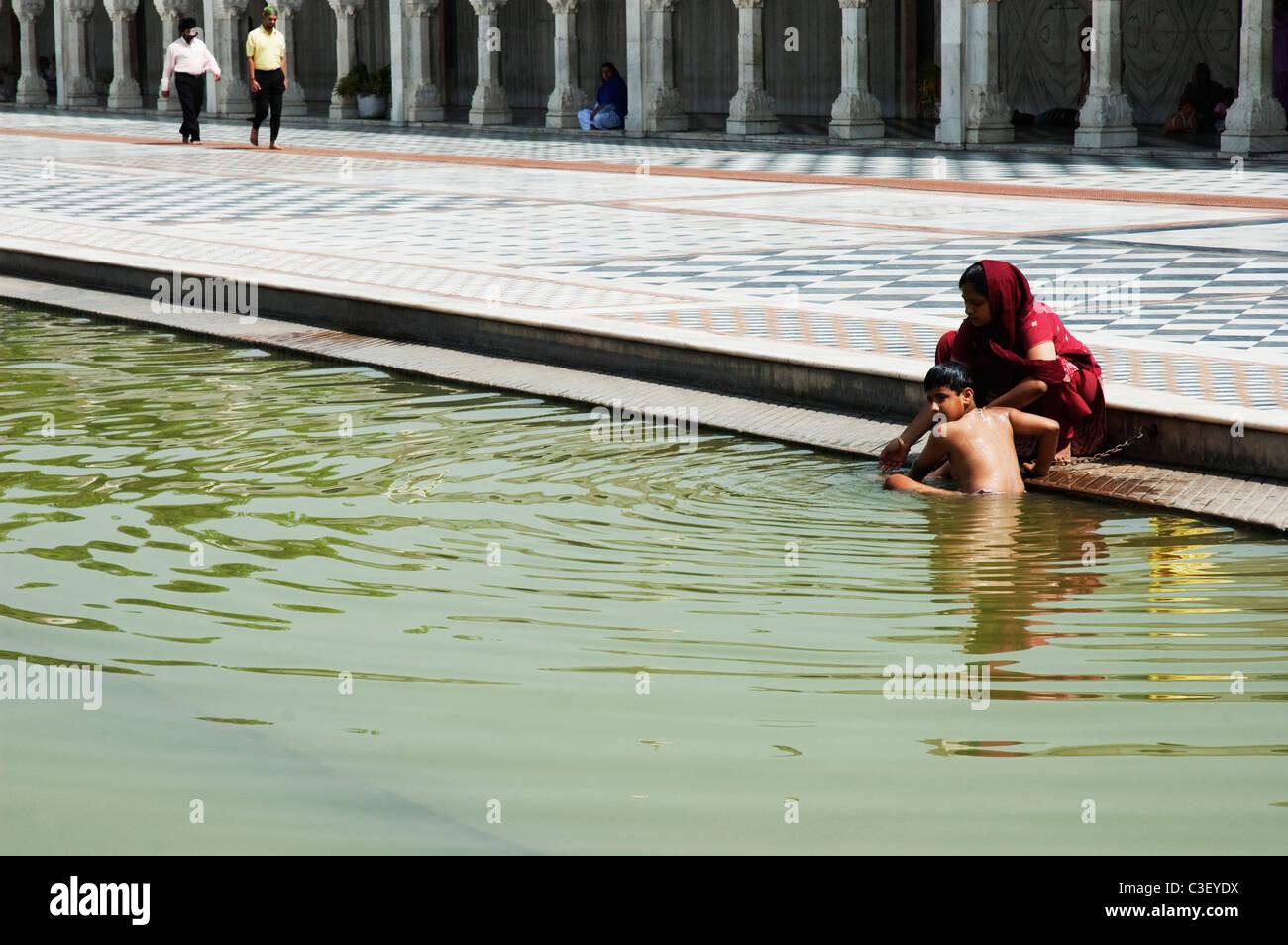 Woman getting her son bath in a pond at a gurudwara, Gurudwara Bangla Sahib, New Delhi, India Stock Photo