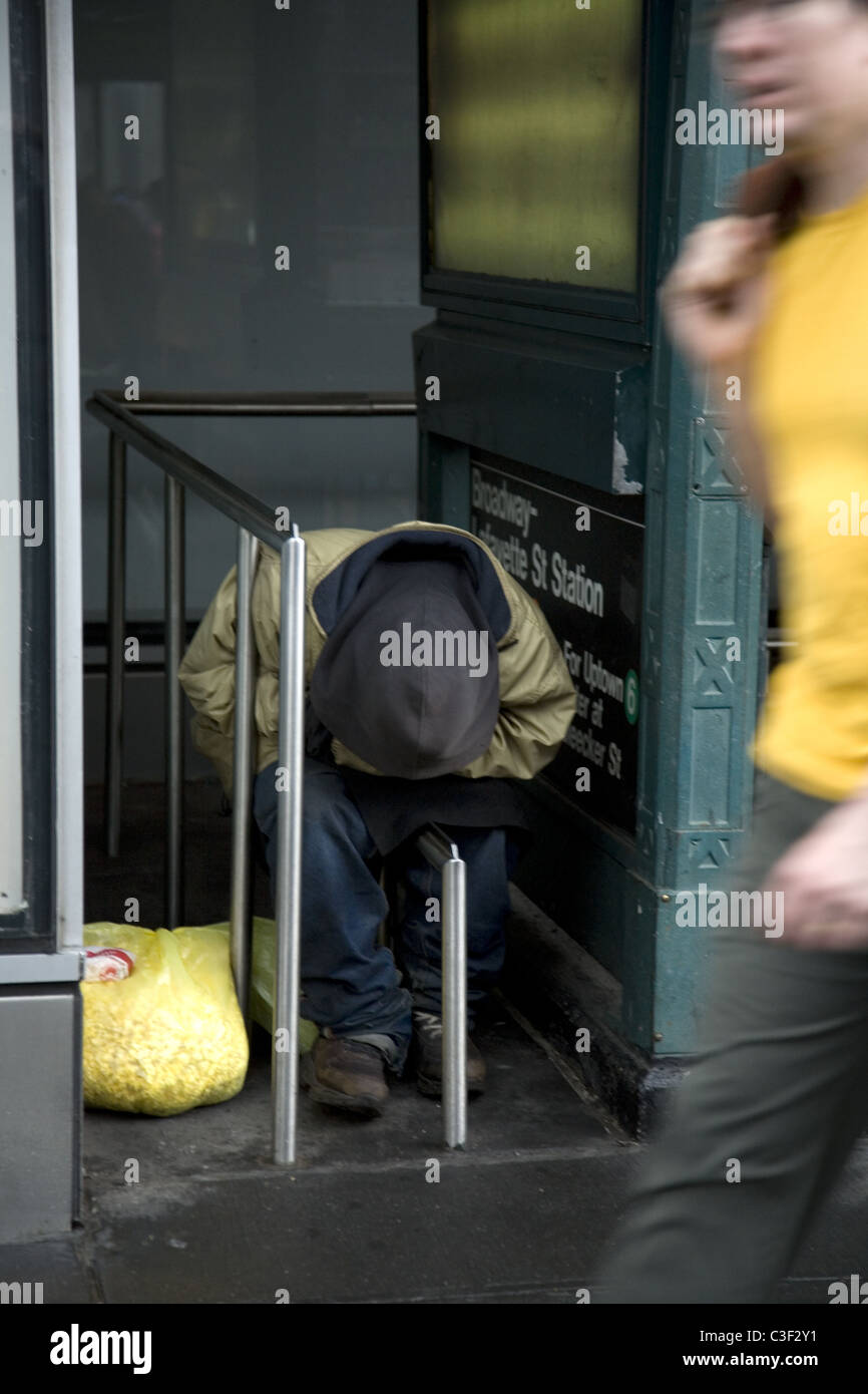 Indigent man sleeping by a subway entrance on Houston Street in SOHO in NYC. - Stock Image