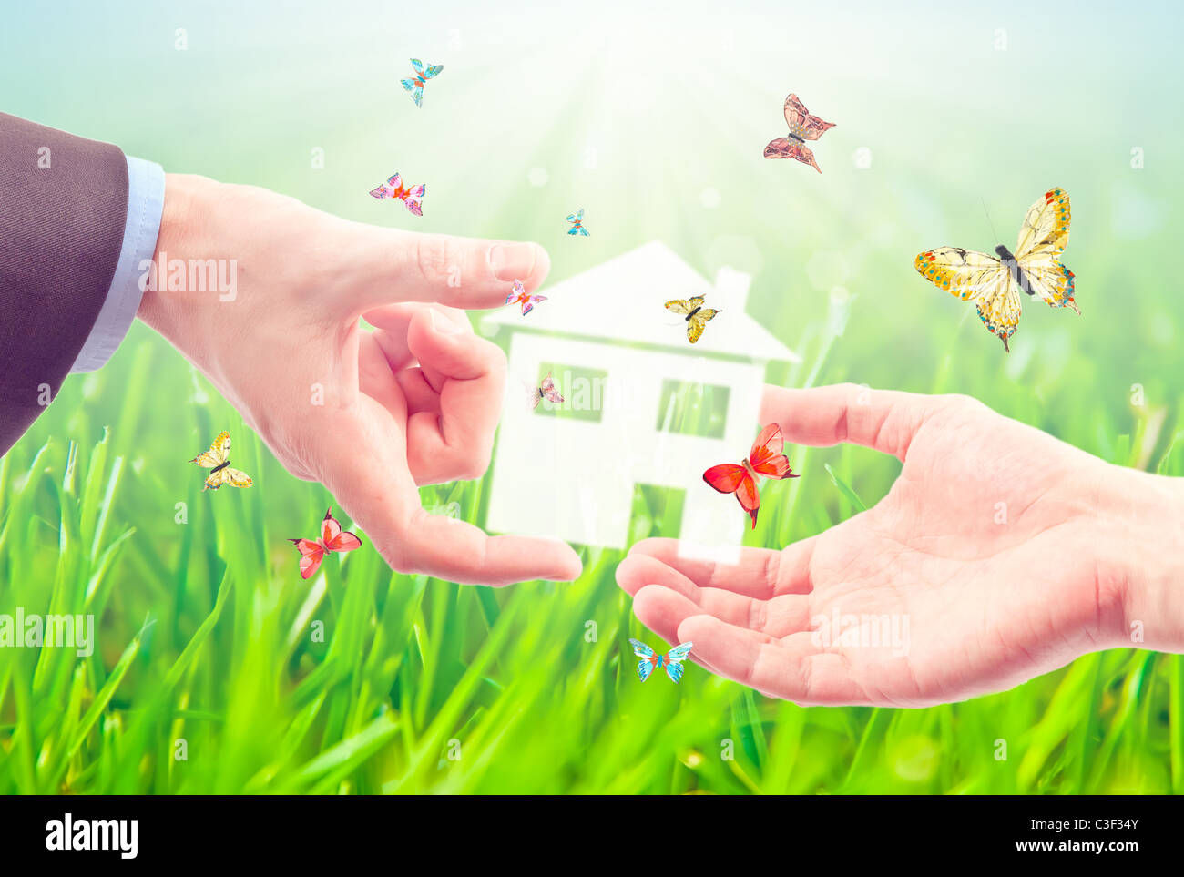 The House in the hands against the blue sky as a symbol of the real estate business. - Stock Image