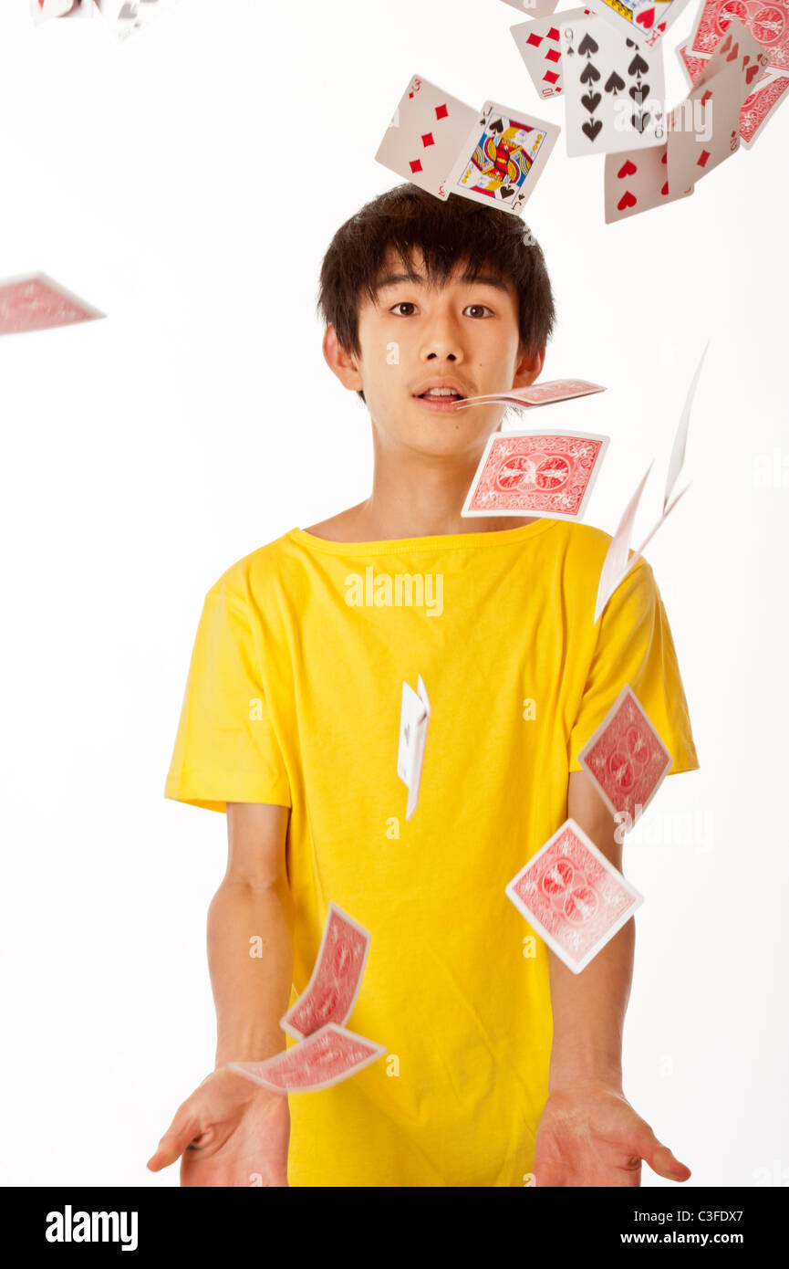 teenage Chinese Asian boy flicking playing cards into the air against white background - Stock Image