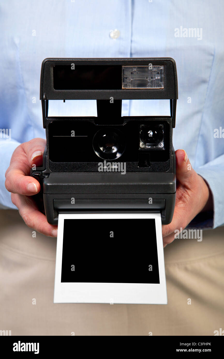 Photo of a woman holding an instant camera with a blank print to add your own image,clipping path included for the - Stock Image