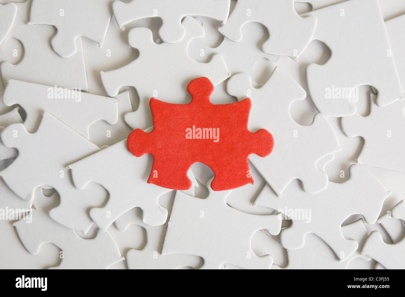 One red jigsaw piece on a pìle of blank ones.  - Stock Image