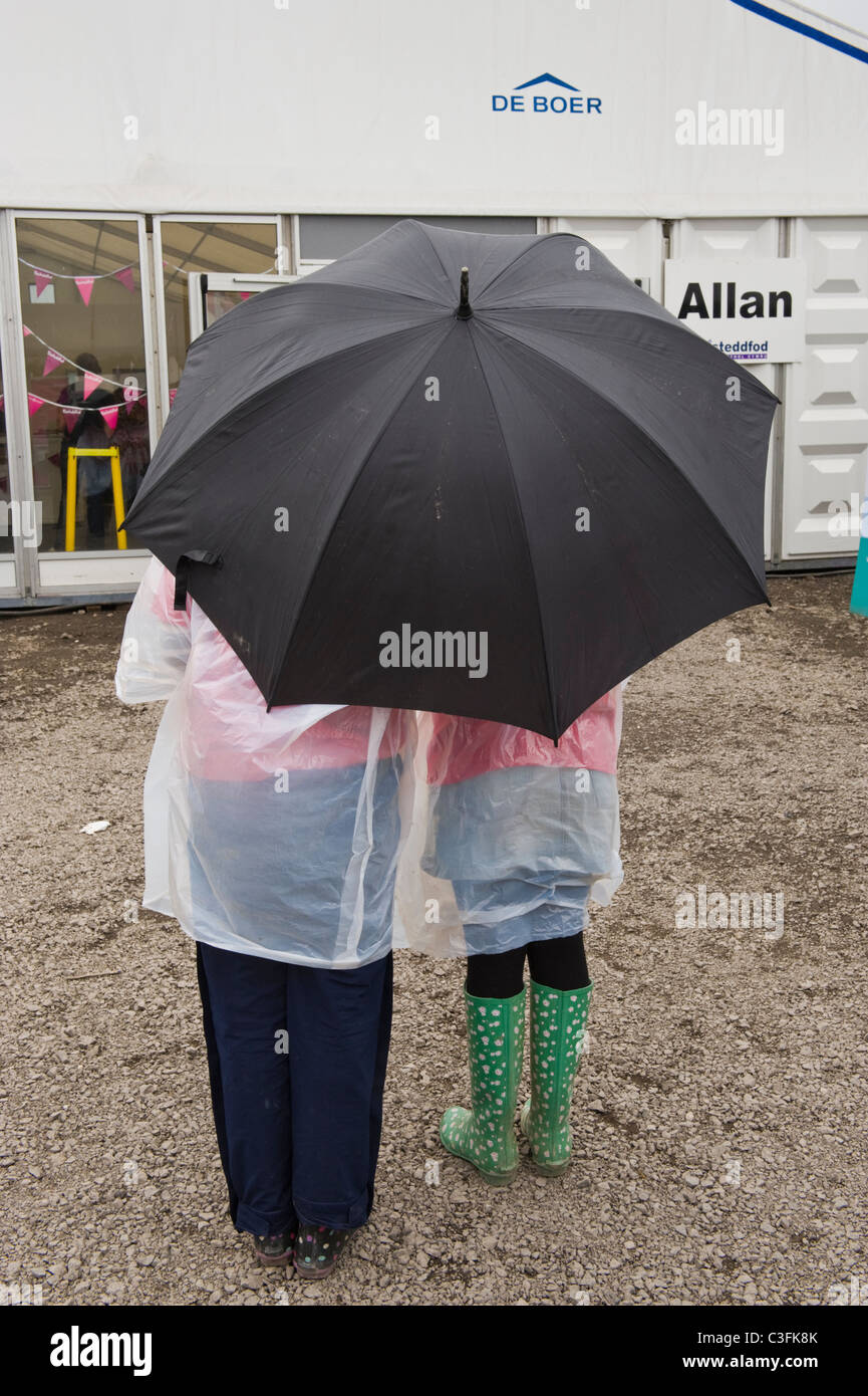 People in wet weather gear at National Eisteddfod 2010 Ebbw Vale Blaenau Gwent South Wales UK - Stock Image