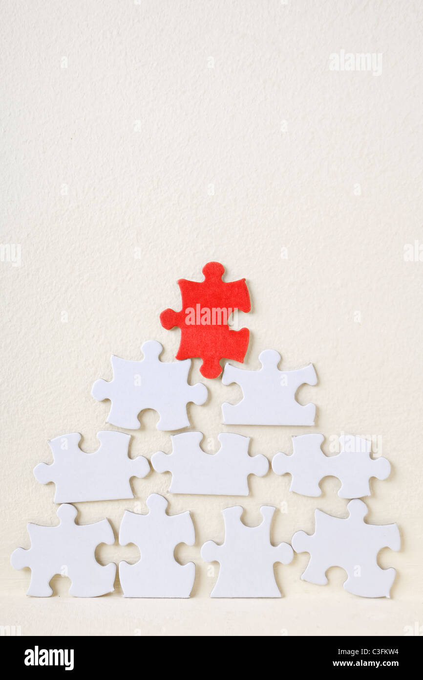 Pyramid of white jigsaw puzzle pieces against a textured wall. Pyramid capped by a red piece - Stock Image