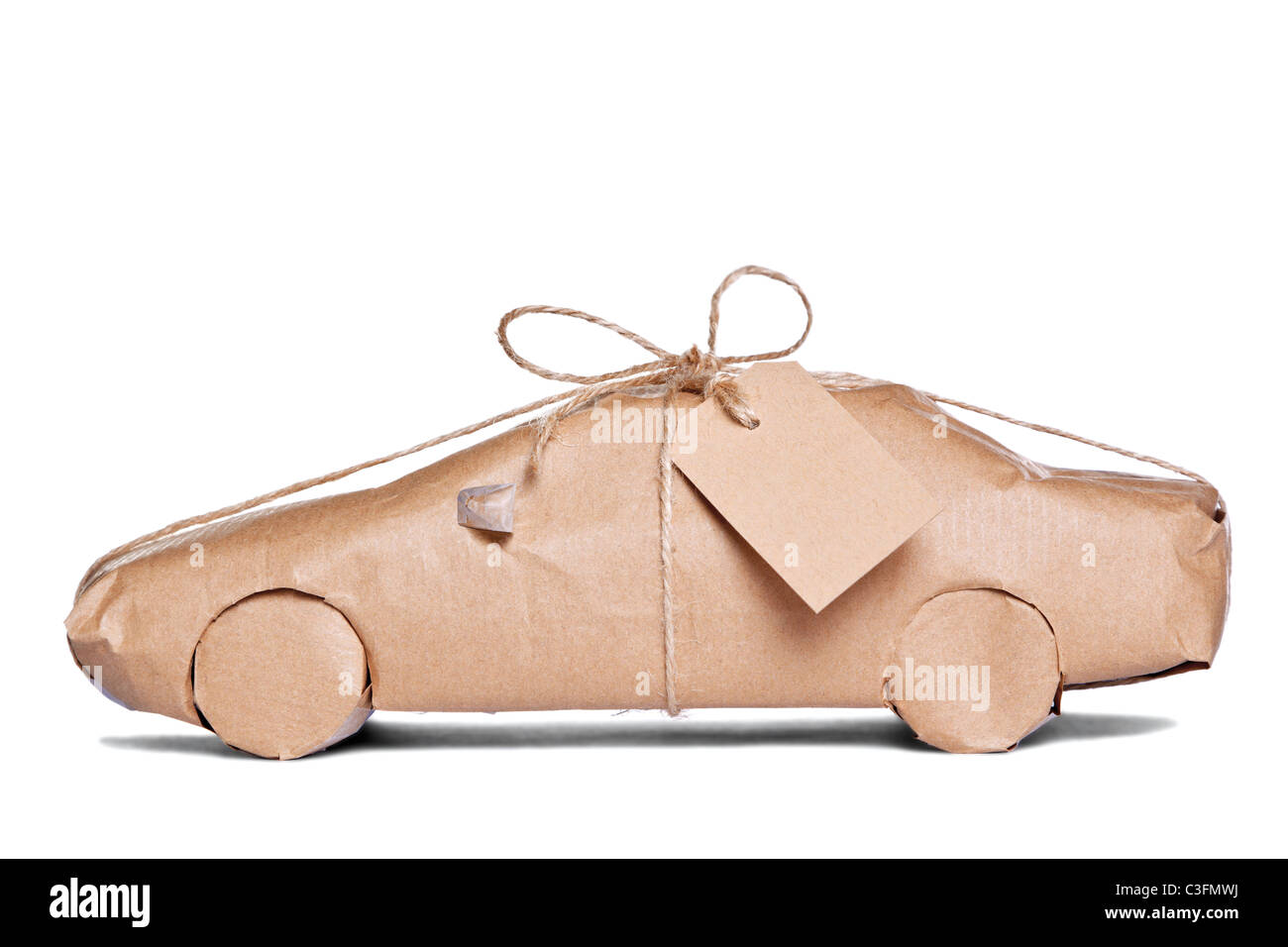 Photo of a car wrapped in brown recycled paper with label, cut out on a white background. - Stock Image