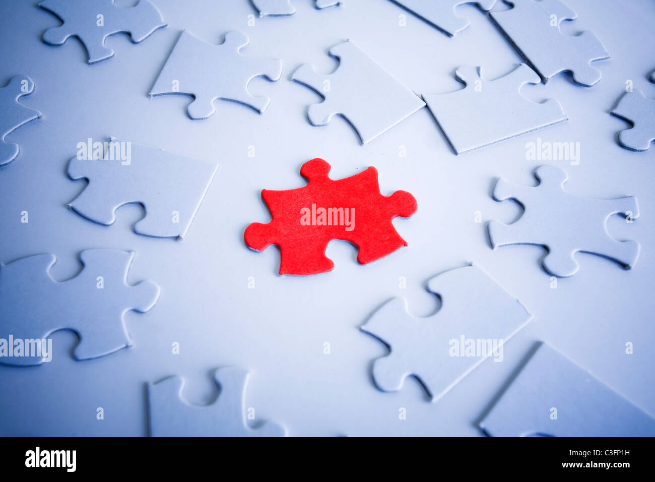 Red jigsaw piece among white pieces. - Stock Image