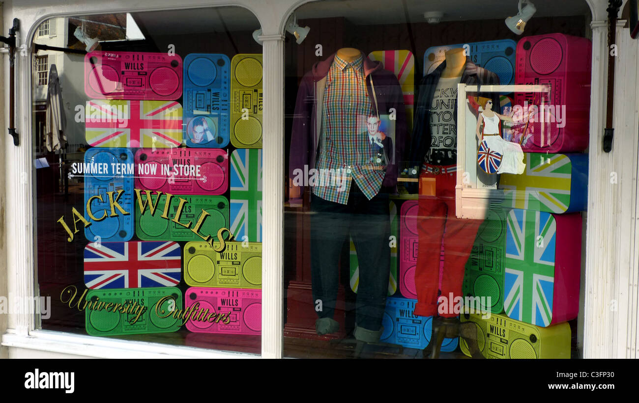 Shop window with multiple variously coloured union jack flags and reflected image of Britannia with shield & - Stock Image