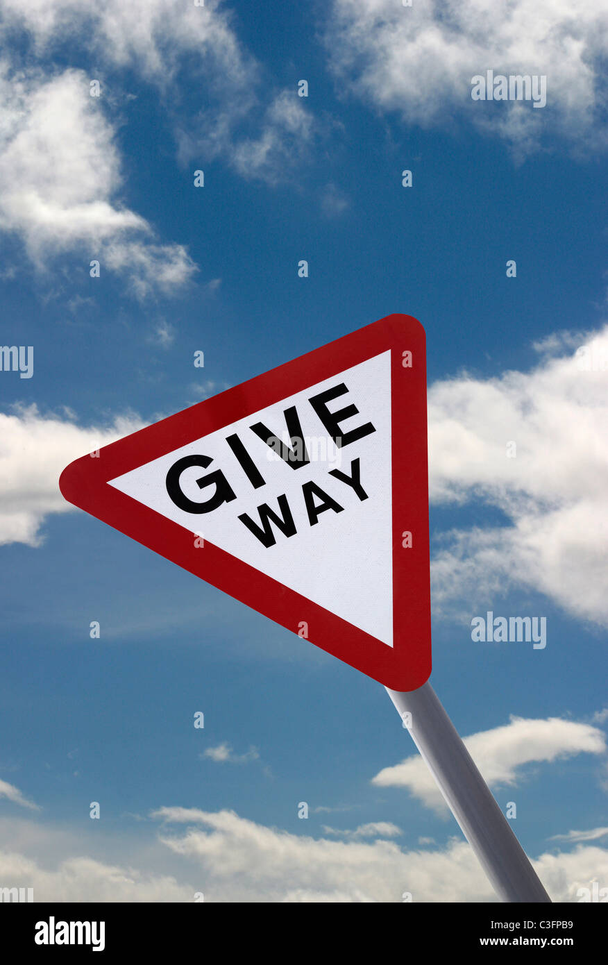 Give way sign in England. Cut out against a Blue sky with white clouds.Portrait image Stock Photo