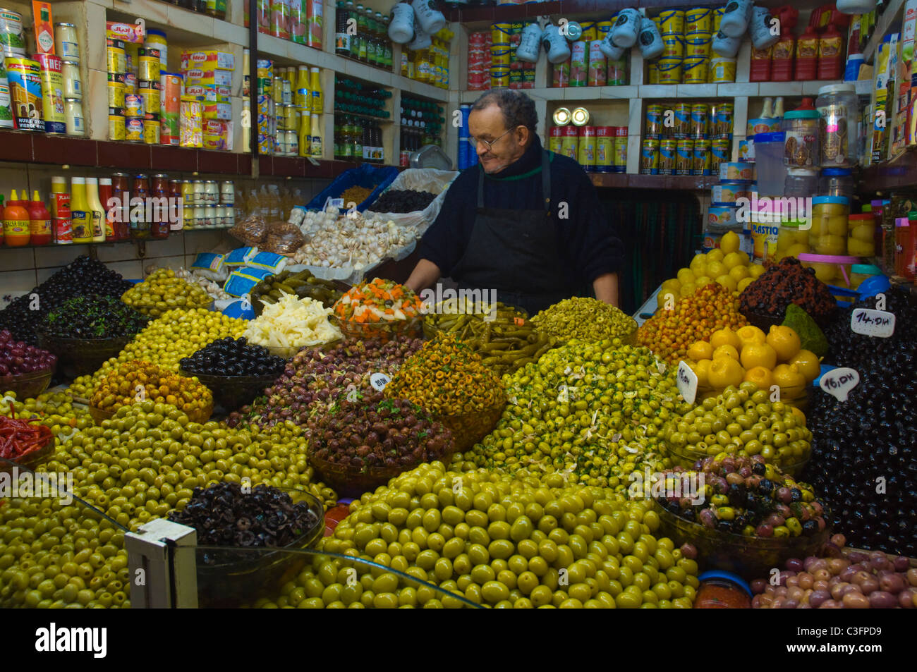 Stall selling olives and other locals foods inside covered markets outside Medina old town Tangier Morocco northern - Stock Image