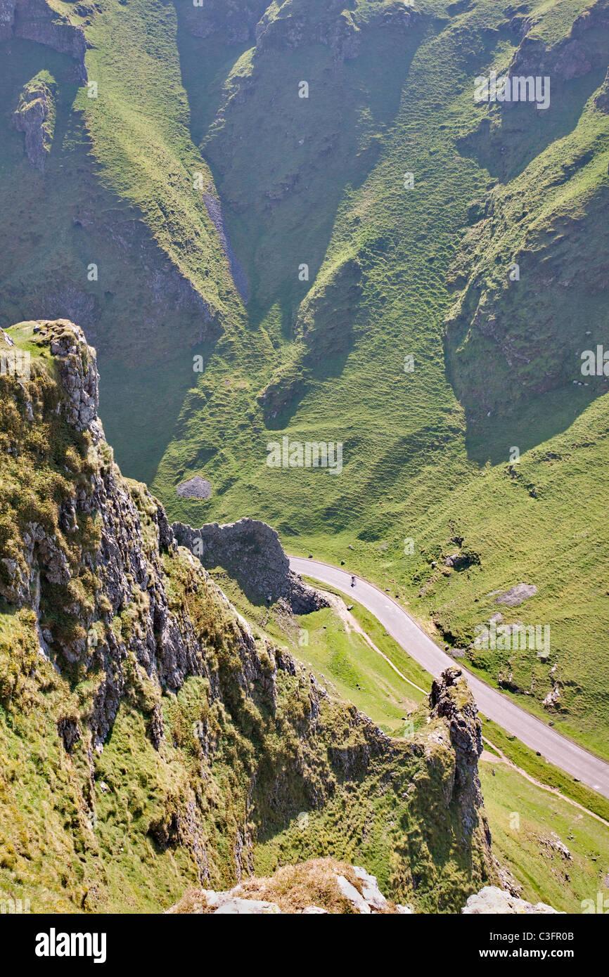 A lone cyclist speeds down the steep limestone gorge of Winnat's Pass near Castleton in the Derbyshire Peak - Stock Image