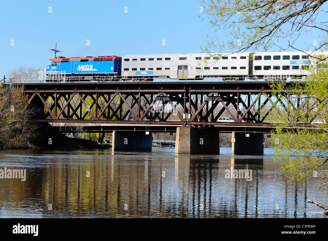 Metra commuter train out of Chicago crossing over the Fox River on rusting bridge. - Stock Image
