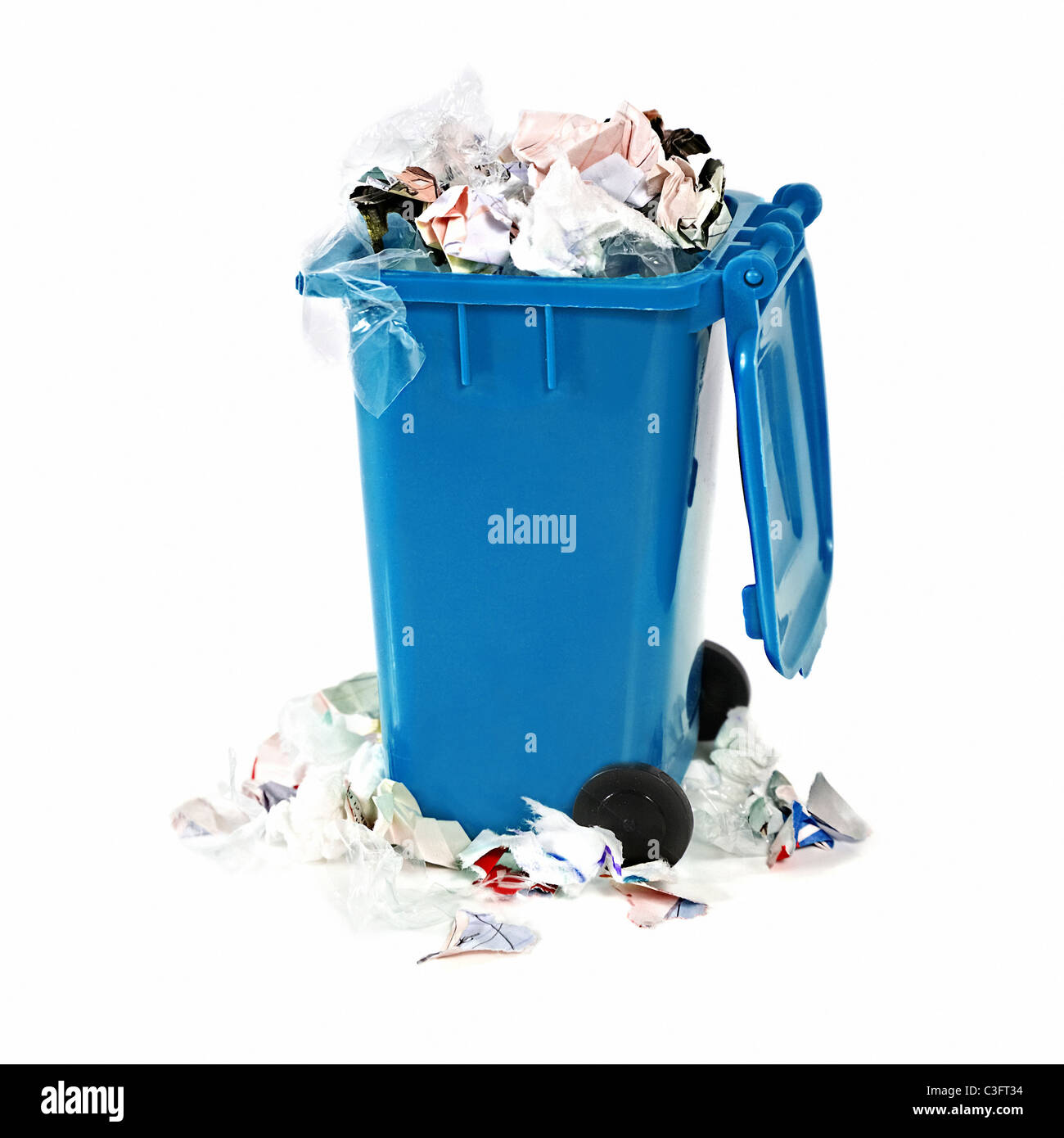 overflowing blue garbage bin on white background - Stock Image