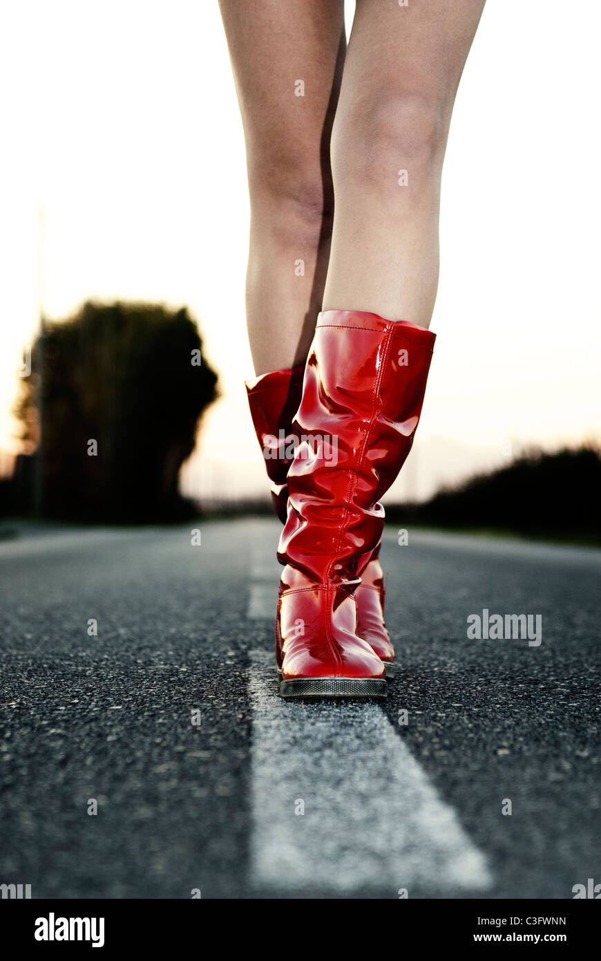 Girl in red wellington boots walking down the road Stock Photo
