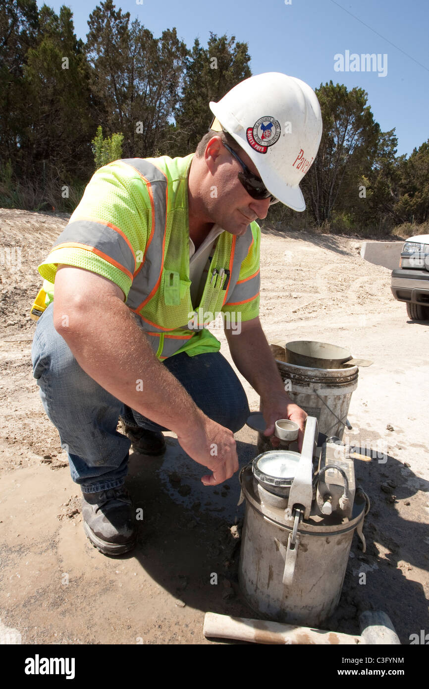 Male Worker uses gage to  measure amount of air in concrete along stretch of highway construction in Austin, Texas Stock Photo