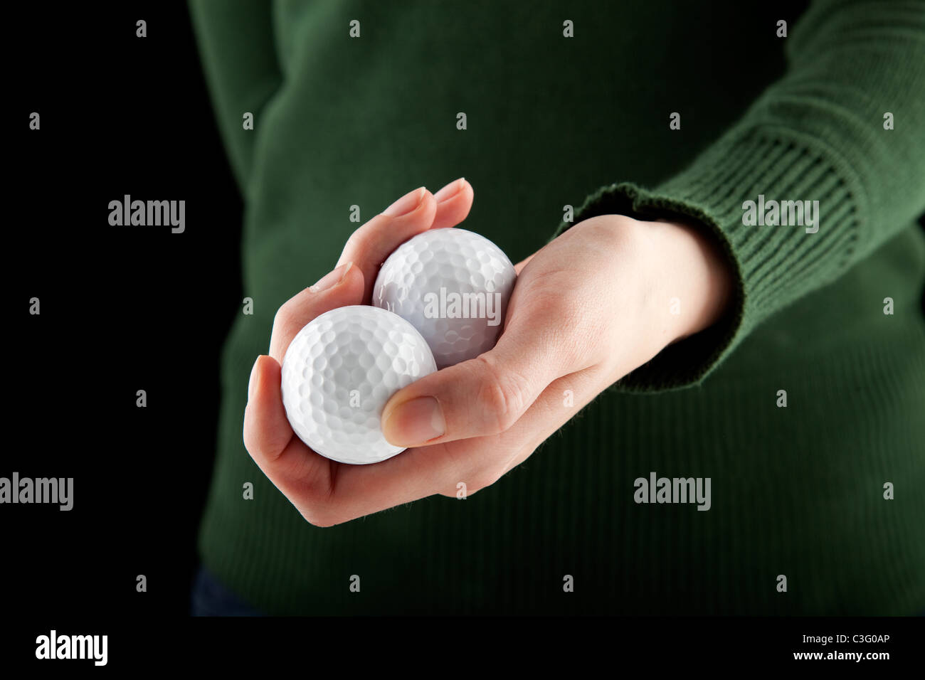 close up shot of a female hand holding two golf balls - Stock Image