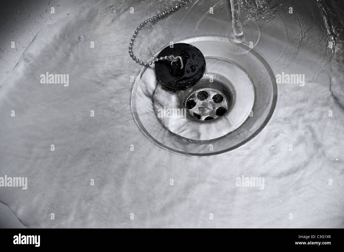 Water Running Down the Plughole in Kitchen Sink - Stock Image