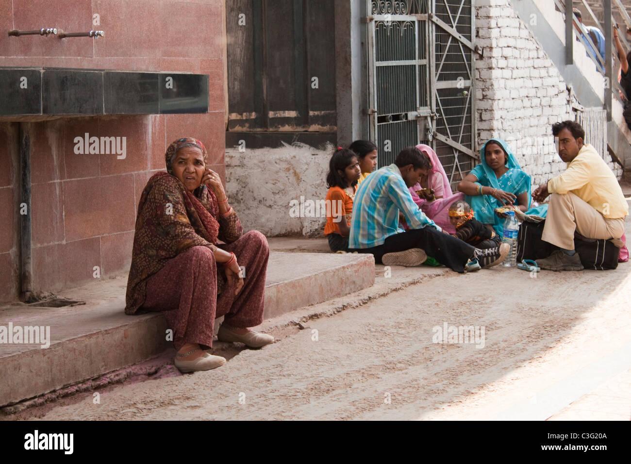 Passengers waiting at a railway station, Ahmedabad, Gujarat, India - Stock Image