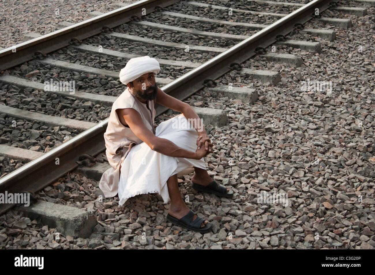 Man sitting near railroad tracks, Ahmedabad, Gujarat, India - Stock Image