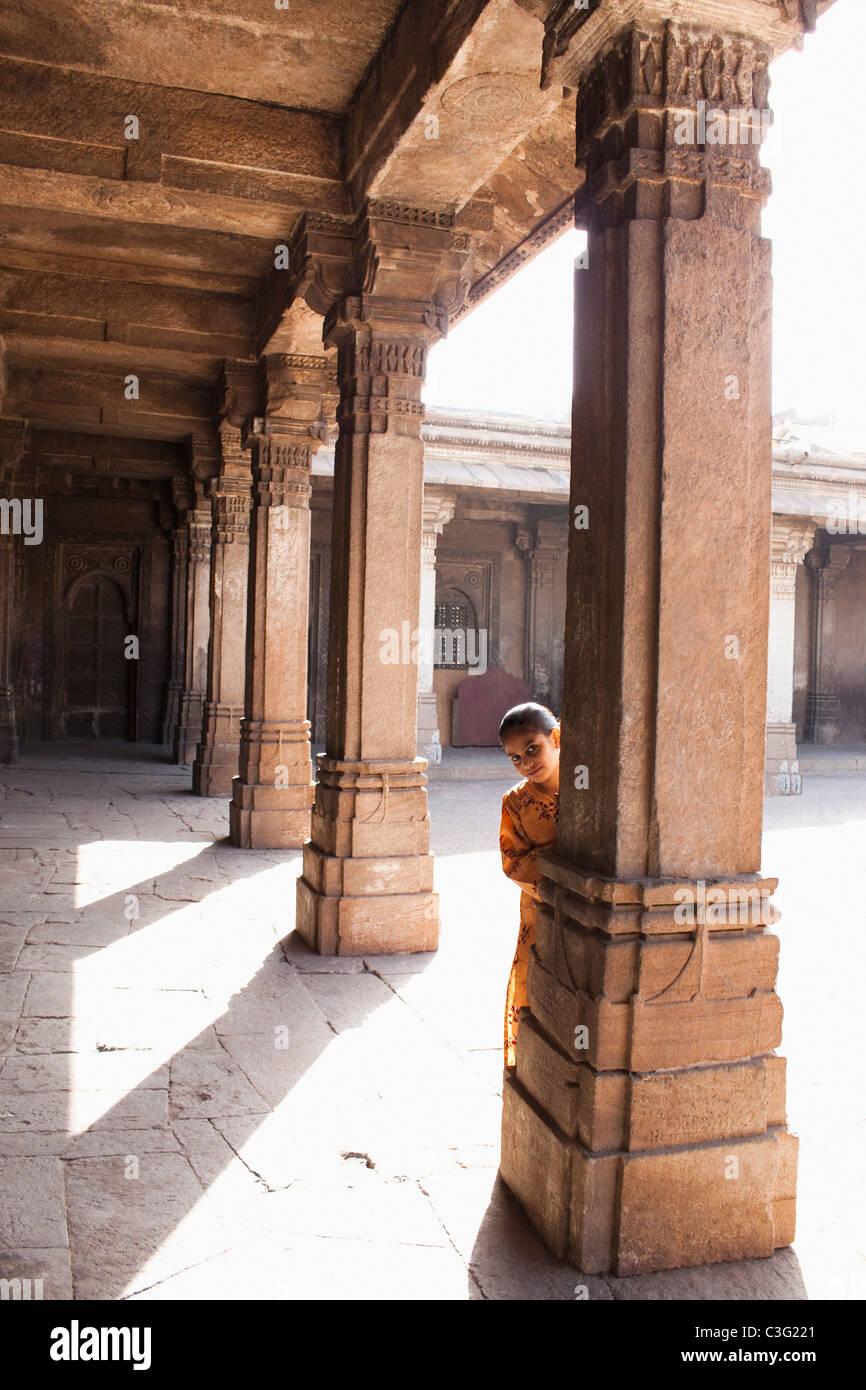 Girl standing behind a column, Ahmedabad, Gujarat, India - Stock Image