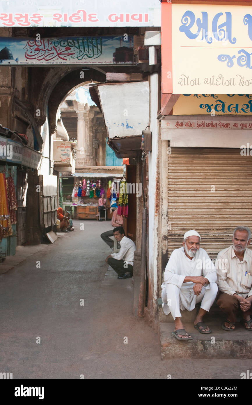 Group of people sitting in a street, Ahmedabad, Gujarat, India - Stock Image