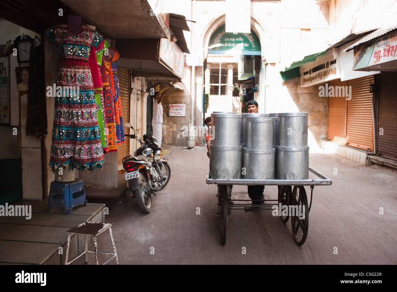 Two men pushing containers on a cart on the street, Ahmedabad, Gujarat, India Stock Photo