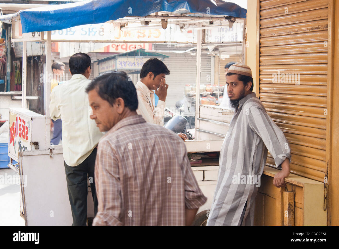 Four men standing in a market, Ahmedabad, Gujarat, India - Stock Image