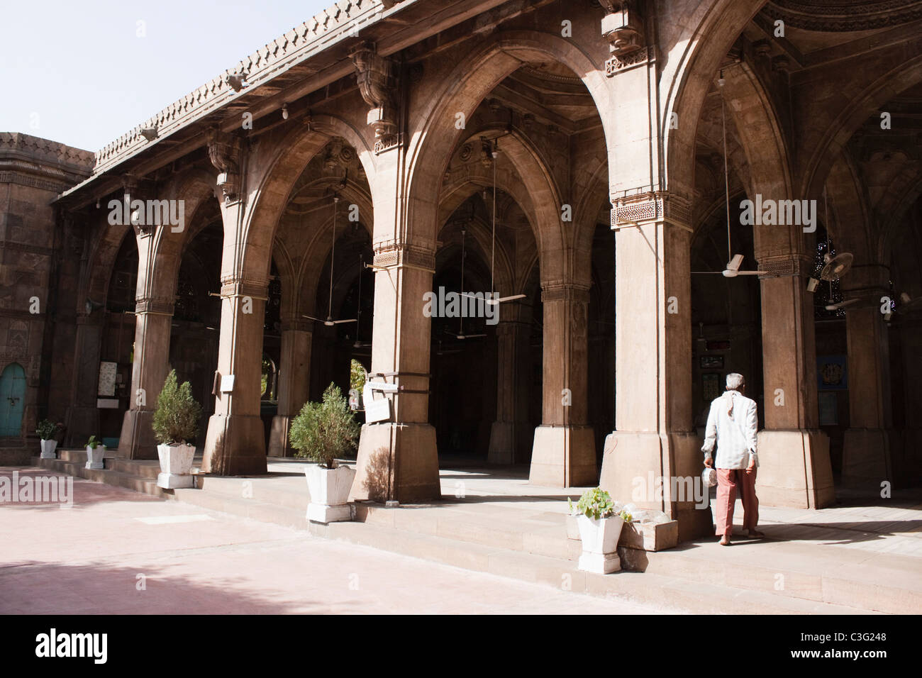Man walking in a mosque, Siddi Sayed Mosque, Ahmedabad, Gujarat, India - Stock Image