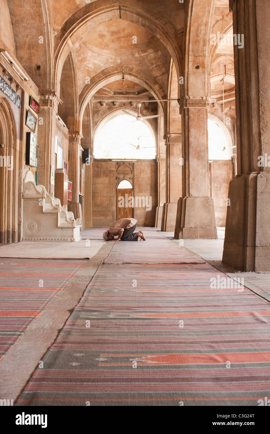 Man praying in a mosque, Siddi Sayed Mosque, Ahmedabad, Gujarat, India - Stock Image