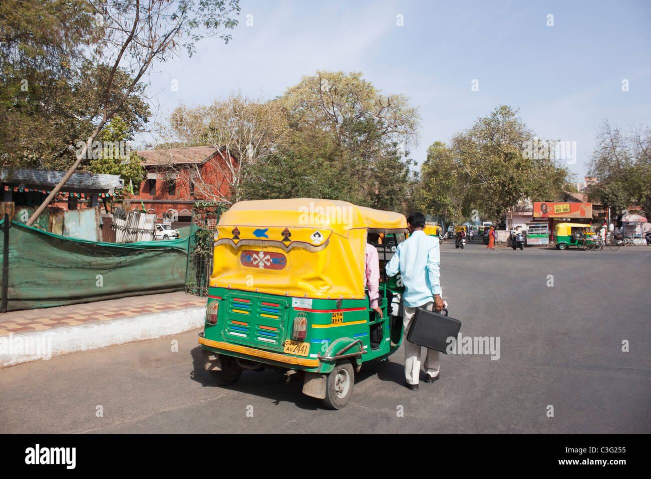 Man standing near an auto rickshaw, Ahmedabad, Gujarat, India - Stock Image