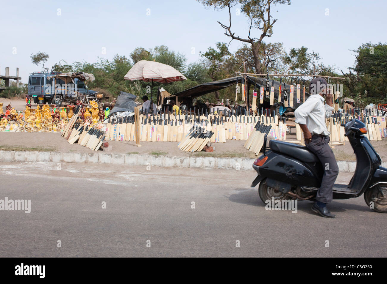 Man sitting on a scooter on the road, Ahmedabad, Gujarat, India - Stock Image