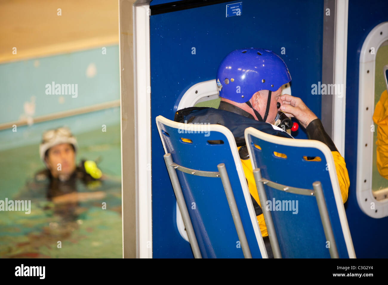 Workers in the offshore industry practice helicopter ditching evacuation as part of an industry training course - Stock Image