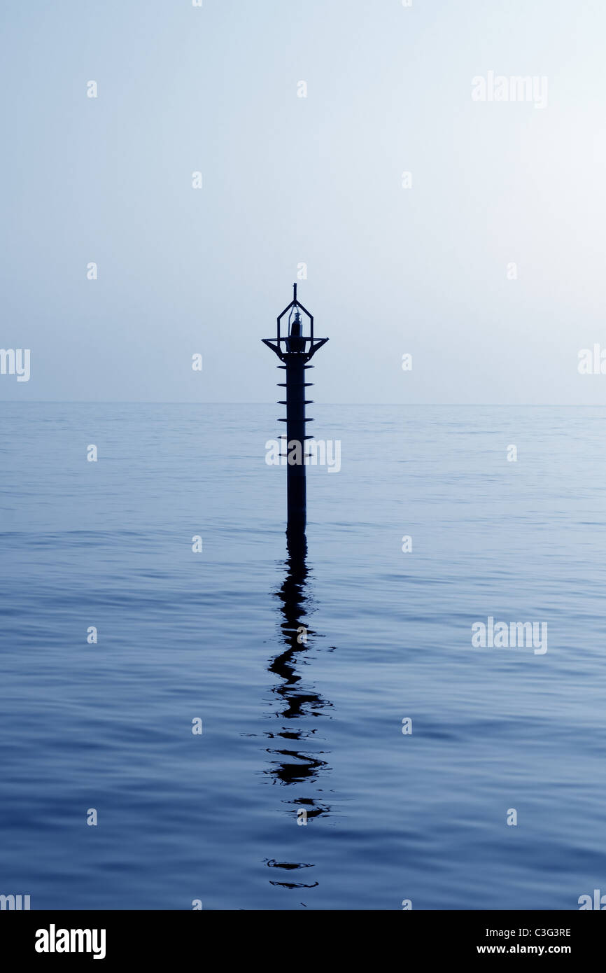 back light navigation beacon in Mediterranean blue sea water reflection - Stock Image