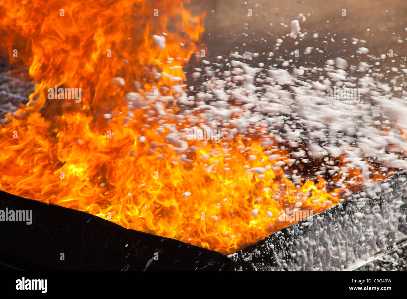 Fighting a fire with a foam fire extinguisher. - Stock Image