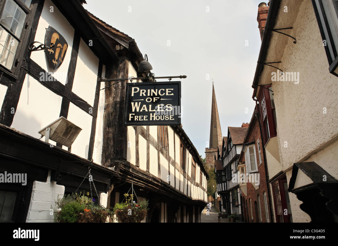 Church Lane Ledbury, Prince of Wales pub sign and church spire in the background. Herefordshire, England, UK - Stock Image